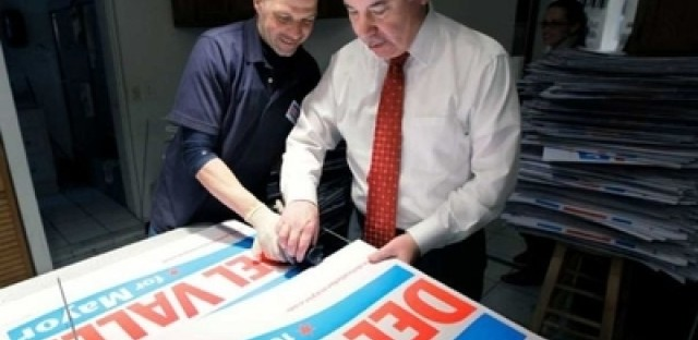 Mayoral candidate Miguel del Valle assembles campaign signs with volunteer Israel Martinez at campaign headquarters.