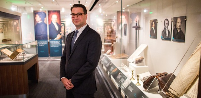 Religion curator Peter Manseau stands in the National Museum of American History's new exhibit, Religion in Early America.