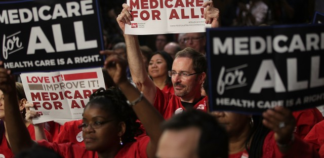 Supporters of Sen. Bernie Sanders, I-Vt., hold signs Wednesday during an event on health care on Capitol Hill.