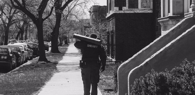 A Cook County sheriff's deputy strolls outside a south-side building with a battering ram, which deputies use to enter units if tenants being evicted aren't home and the landlord doesn't have a key.