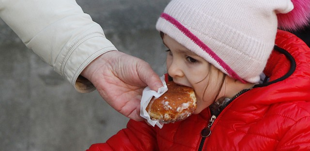 A little girl indulges in Poland's tradition of eating jam-filled doughnuts, or paczki, after having stood in line for some three hours to get the cakes traditionally eaten on the last Thursday of carnival, the Fat Thursday in Warsaw, Poland, Feb. 27, 2014.