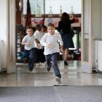 In this Tuesday, June 7, 2016 photo, students run to go outside at the start of a recess between classes at Little Fort Elementary school in Waukegan, Ill. Over the past five years, Waukegan District 60 lost $43 million in state aid because Illinois cut education funding, according to Gwendolyn Polk, associate superintendent of business and financial services.