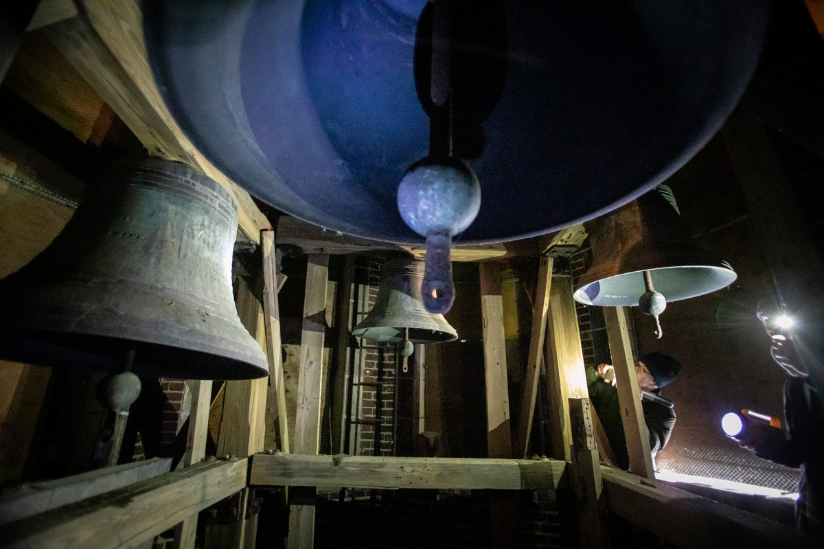 Bells at the top of the bell tower in the Stockyard bank building. They are lit by flashlights and dusty.