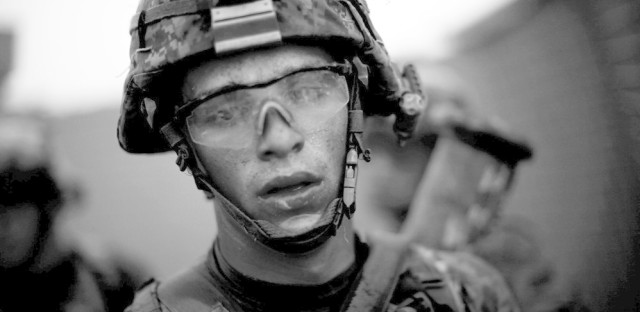 """Bravo Company's Pvt. Cody Lee Ensley walks through the safety of the gates at an American base after a daylong fierce attack by insurgents near Payendi. From the story """"Signs Of Traction In U.S. Fight Against Afghan Taliban,"""" 2010."""