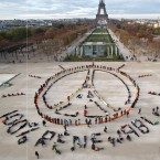 "Environmentalist activists form a human chain representing the peace sign and the spelling out ""100% renewable"", on the side line of the COP21, United Nations Climate Change Conference near the Eiffel Tower in Paris, Sunday, Dec. 6, 2015. Negotiators adopted a draft climate agreement Saturday that was cluttered with brackets and competing options, leaving ministers with the job of untangling key sticking points in what is envisioned to become a lasting, universal pact to fight global warming."