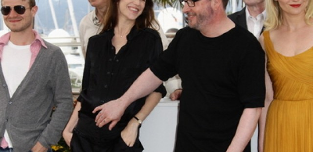 Director Lars Von Trier (2R) touches the pregnant stomach of actress Charlotte Gainsbourg as they attend 'Melancholia' at Cannes