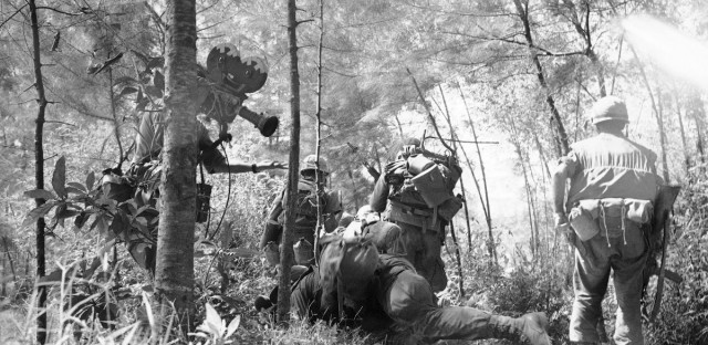 Marines charge against a sniper down the trail of Phu Thu peninsula southeast of Hue in March 1966. And at left, behind a tree is a television cameraman filming the action.
