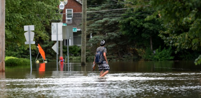 "A man walks on a flooded street Friday, July 14, 2017, in Gurnee, Ill. Illinois officials said Friday that several thousand buildings have been affected by ""unprecedented"" flooding north of Chicago, and the damage is expected to worsen this weekend as water flows down rivers into the state from Wisconsin."