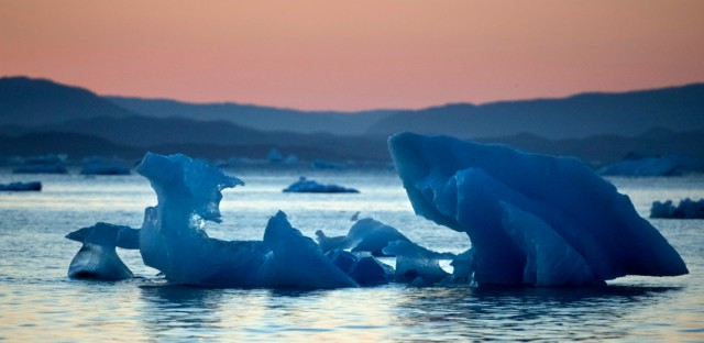 The suns sets as an iceberg floats in the Nuup Kangerlua Fjord near Nuuk in southwestern Greenland on Aug. 1, 2017. Greenland's glaciers have been melting and retreating at an accelerated pace in recent years due to warmer temperatures. If all of that ice melts, sea levels will rise by several meters, though there will be regional differences.