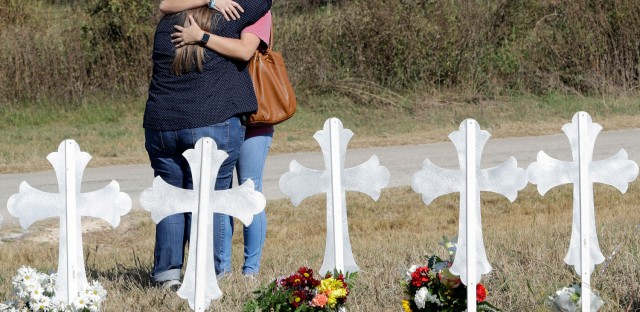 Two women hug at a makeshift memorial for the First Baptist Church shooting victims in Sutherland Springs, Texas. (David J. Phillip/AP)