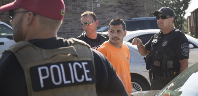 Immigration and Customs Enforcement officers and Fort Worth police officers detain an unauthorized immigrant from Mexico at an apartment complex.