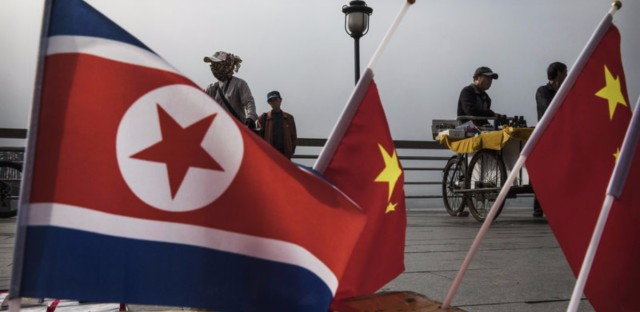 A China-based tour company says it will no longer take U.S. citizens to North Korea. Here, Chinese vendors sell flags of North Korea and China along the Yalu river in Dandong, northern China, along the border with North Korea.