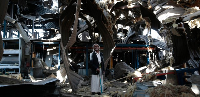In this Sept. 22, 2016 photo, Massoud Abdullah Azzan, 75, who is a doorkeeper, stands amid the rubble of Alsonidar Group's water pumps and pipes factory after it was hit by Saudi-led airstrikes, in Sanaa, Yemen. In the air campaign by Saudi Arabia and its allies against Yemen's Shiite rebels, rights experts say there has been a pattern by the Saudi-led coalition in depending on faulty intelligence, failing to distinguish between civilian and military targets and disregarding the likelihood of civilian casualties. Experts say some of the strikes likely amount to war crimes.