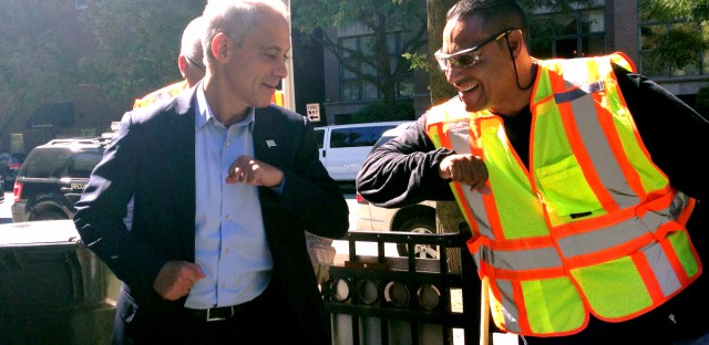 Mayor Rahm Emanuel gives an elbow-bump to a Chicago Department of Streets & Sanitation worker.