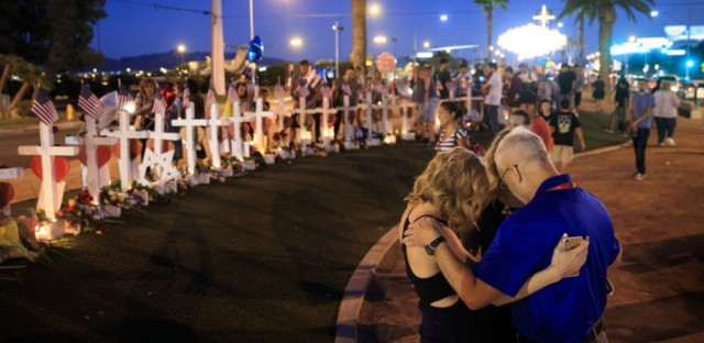 A small group prays at a makeshift memorial for victims of the Las Vegas massacre.