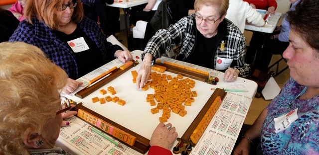 A group of women play in a mah jongg tournament in Ohio to coincide with an exhibit curated by Melissa Martens.