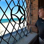 In this Oct. 19, 2015 photo, developer Chuck Williams, a state Republican Party official, looks at the Lake Michigan shoreline through a window in the dilapidated beachfront pavilion at Indiana Dunes State Park in Chesterton, Ind., that he plans to rehabilitate. Williams is warning that Indiana could owe him millions of dollars if officials scuttle his contract to bring fine dining, a banquet hall and bar to a lakefront state park surrounded by the state's towering dunes.