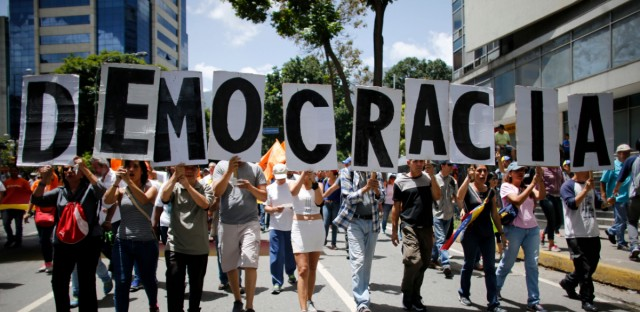 "Anti-government demonstrators hold a poster that reads in Spanish ""Democracy"" during a protest against Venezuela's President Nicolas Maduro in Caracas, Venezuela, Saturday, Aug. 12, 2017. Opposition members called a demonstration to protest the seating of a special assembly to rewrite the constitution. Observers will be closely watching the turnout as the arrest of several mayors and the opposition's decision to compete in regional elections despite concerns the election for the constitutional assembly was marred by fraud."