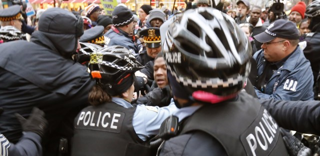 Chicago Police officers take a protester into custody during a scuffle at a police bicycle barricade on Chicago's Magnificent Mile Thursday, Dec. 24, 2015, in Chicago. The Christmas Eve Day protest calling for the resignation of Mayor Rahm Emanuel is the latest in a series of demonstrations in the city since the release last month of police video showing a white officer shoot a black teenager 16 times.