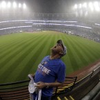 "An unnamed Chicago Cubs fan catches raindrops in his mouth after the Cubs finally won the World Series on Wednesday. His shirt says, ""Just one before I die."""
