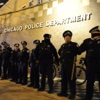 Chicago police officers line up outside the District 1 central headquarters at 17th and State streets, Tuesday, Nov. 24, 2015, in Chicago, during a protest for 17-year-old Laquan McDonald, who was fatally shot and killed in October 2014. Chicago police Officer Jason Van Dyke was charged Tuesday with first-degree murder in the killing.