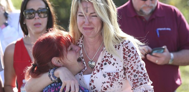 Parents wait for news after a shooting at Marjory Stoneman Douglas High School in Parkland, Fla., on Wednesday. Officials say 17 people were killed and a suspect is in custody.