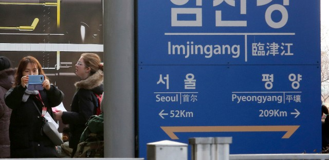 A woman takes pictures in front of a signboard showing the distance to the North Korea's capital Pyongyang and to South Korea's capital Seoul from Imjingang Station in Paju, South Korea, near the border with North Korea, Thursday, Jan 4, 2018. North Korean leader Kim Jong Un reopened a key cross-border communication channel with South Korea for the first time in nearly two years Wednesday as the rivals explored the possibility of sitting down and talking after months of acrimony and fears of war.