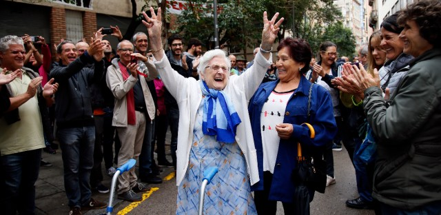 An elderly lady is applauded as she celebrates after voting at a school assigned to be a polling station by the Catalan government at the Gracia neighborhood in Barcelona, Spain, on Sunday, Oct. 1, 2017. (AP Photo/Bob Edme, File)