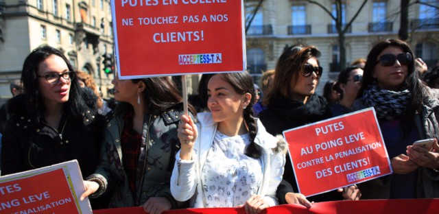 """Protesters hold signs reading, """"Prostitutes are angry. Don't touch our clients,"""" during a protest Wednesday in Paris against legislation combating prostitution and sex trafficking."""