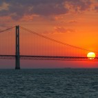 In this May 31, 2002 file photo, the sun sets over the Mackinac Bridge and the Mackinac Straits as seen from Lake Huron. The bridge is the dividing line between Lake Michigan to the west and Lake Huron to the east.