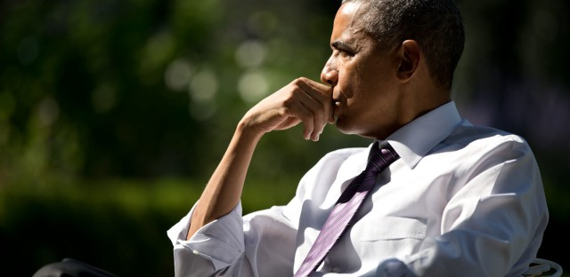 The president listens during a meeting with staff in the Rose Garden on Oct. 8, 2014.