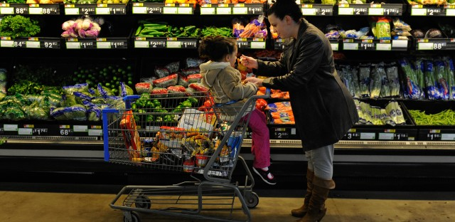 """Rebecka Ortiz offers her daughter a pasta sample at the store where she was using her food stamps to stock up on food for her family in Woonsocket, R.I. The Trump administration is proposing drastic changes in the """"food stamp"""" program, now called SNAP. People getting that aid would lose much of their ability to choose the food they buy."""