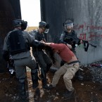 Israeli border policemen detain a foreign activist by the Israeli separation barrier, during a protest in the West Bank village of Bil'in, west of Ramallah, Friday, March 2, 2018. Palestinian protesters and foreign activists marched to commemorate the 13th anniversary of the ongoing weekly protests against the Israeli separation barrier and settlements in Bil'in.