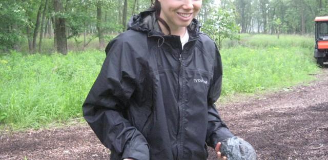 Britt Willey holds two heavy chucks of slag found at Hegewisch Marsh.