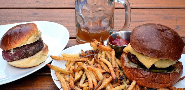 Off-the-menu raw burger, mulled cider with rum, and Red Door Burger with Butterkäse cheese, bacon-onion jam, and tarragon pickles, with hand-cut fries at Red Door kitchen and bar in Chicago