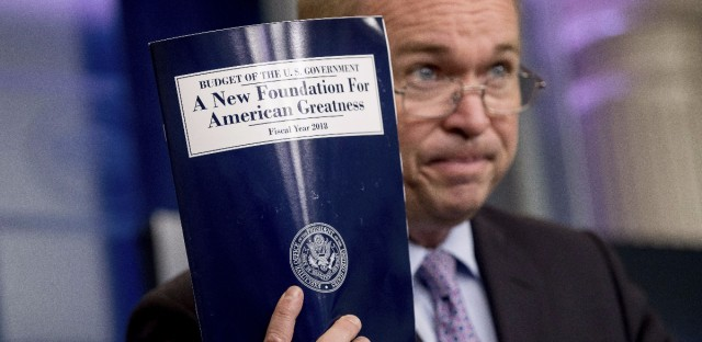 Budget Director Mick Mulvaney holds up a copy of President Donald Trump's proposed fiscal 2018 federal budget at the White House on Tuesday. Andrew Harnik/AP