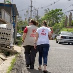 Mercy Corps staffers Jill Morehead (left) and Alexa Swift walk up a hill in Lares as part of their field research on Puerto Rico's supply needs.