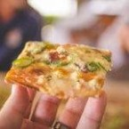 Person holding up a delicious looking slice of pizza to their friends. Pizza Farms pbs rewire