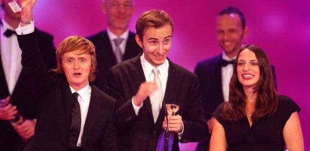 Jan Boehmermann, center, holds an award for the category best comedy during the 2009 German Television award ceremony in Cologne.