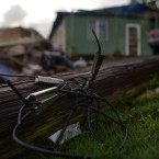 In this Dec. 22, 2017 photo, a light pole knocked down by the winds of hurricane María remains on the ground in front of the house of the Oliveras González family, in Morovis, Puerto Rico.