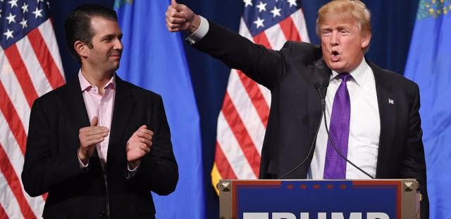 Donald Trump Jr. looks on as his father, then-GOP presidential candidate Donald Trump, waves after speaking at a caucus night watch party at the Treasure Island Hotel & Casino in Las Vegas, Nev., in February 2016. (Ethan Miller/Getty Images)