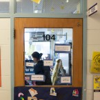 Stickers and nametags cover a classroom door at Beulah Shoesmith Elementary School in Chicago. A teacher is seen through teh door