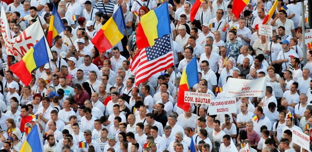 Supporters of the ruling Social Democratic attend a rally outside the government headquarters in Bucharest, Romania, Saturday, June 9, 2018. More than 100,000 supporters of the Romanian government assembled Saturday in the capital dressed in white to protest alleged abuses committed by anti-corruption prosecutors