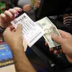 Biren Shah, right, sells a Powerball lottery ticket to a patron at his news stand as the multi-state jackpot reaches $800 million, Friday, Jan. 8, 2016, in Chicago. With ticket sales doubling previous records, the odds are growing that someone will win Saturday's record jackpot, but if no one wins the top prize, next week's drawing is expected to soar past $1 billion.