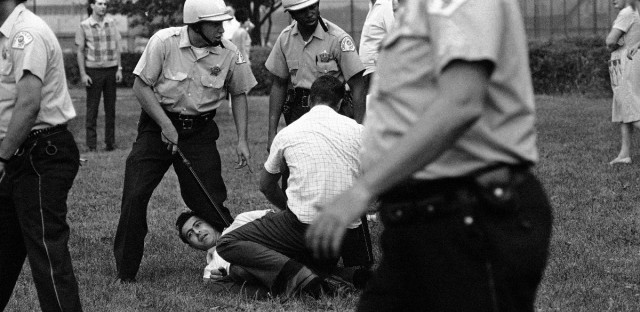 A Chicago policeman, using his knee and nightstick to restrain a man, wait for a police van to take him away. He was arrested during a civil rights march through a white residential neighborhood on Chicago's Northwest Side, Aug. 7, 1966. (AP Photo/Larry Stoddard)