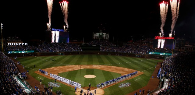Fans and players stand as they watch fireworks during the national anthem in the opening ceremonies for the Chicago Cubs before their home opener against the Los Angeles Dodgers on April 10, 2017, in Chicago. (AP Photo/Nam Y. Huh)