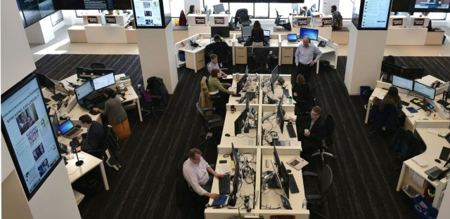 Journalists at The Washington Post work in a newsroom surrounded by screens showing its website and updated reader metrics. (Mandel Ngan/AFP/Getty Images)