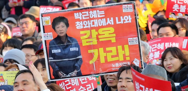"Protesters attend a rally calling for impeached President Park Geun-hye's arrest in Seoul, South Korea on March 11, 2017. South Korean police on Saturday braced for more violence between opponents and supporters of ousted President Park Geun-hye, who was stripped of her powers by the Constitutional Court over a corruption scandal that has plunged the country into a political turmoil. The signs read ""Go to prison."" (AP Photo/Ahn Young-joon)"