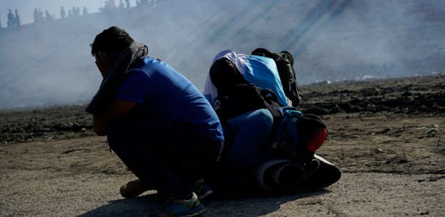 Three Honduran migrants huddle in the riverbank amid tear gas fired by U.S. agents on the Mexico-U.S. border after they and a group of migrants got past Mexican police at the Chaparral border crossing in Tijuana, Mexico, Sunday, Nov. 25, 2018. The mayor of Tijuana has declared a humanitarian crisis in his border city and says that he has asked the United Nations for aid to deal with the approximately 5,000 Central American migrants who have arrived in the city.