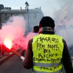 """A demonstrator wearing a yellow vests reading """"Macron, Santa Claus for the rich, enemy of the French people"""" takes part to a demonstration called by the CGT (General Working Confederation) union, Tuesday, Feb. 5, 2019 in Paris. Workers, public servants, and retired people were invited to march during a strike called by the CGT (General Confederation of Labor) union."""